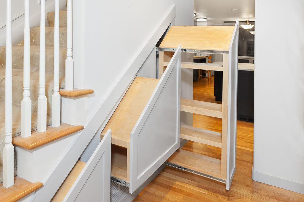 Under-stair pullout cabinets installed in openings with decorative fronts attached, but no handles.
