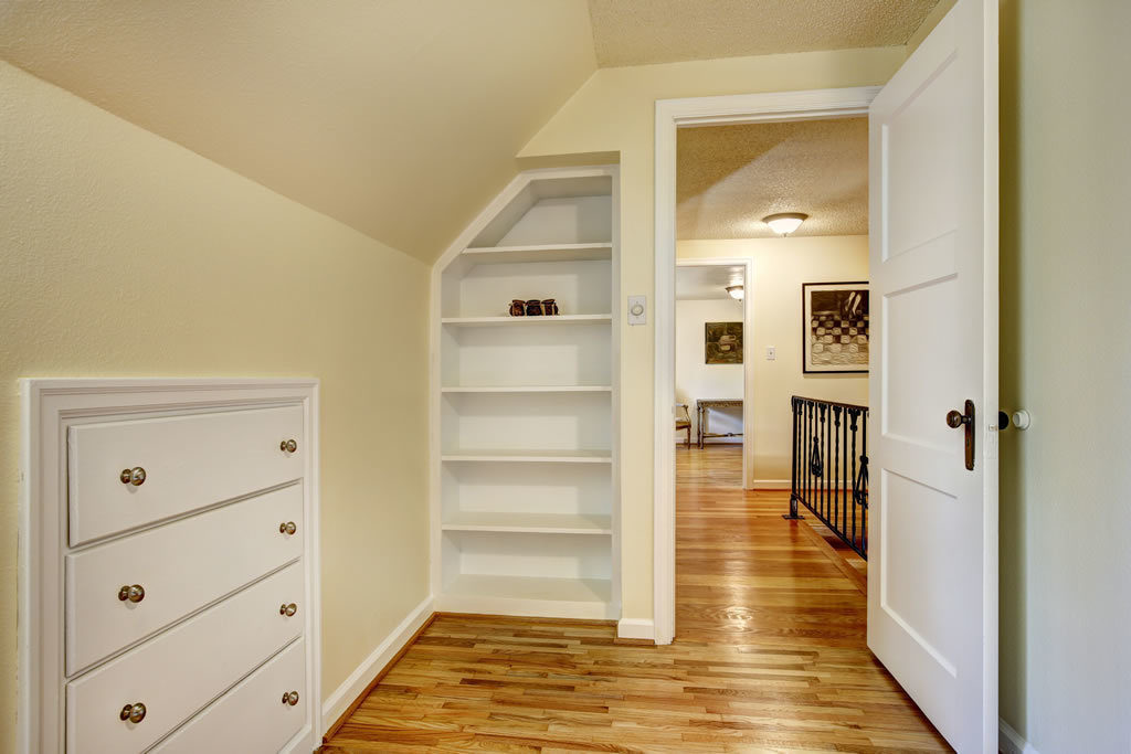 Room with vaulted ceiling, built-in bookshelves and drawers